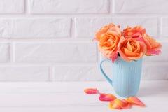 Roses oranges fraîches dans la tasse bleue sur le fond en bois blanc Image libre de droits
