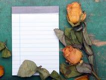 Roses oranges sèches et carnet vide sur le fond en bois, Photographie stock