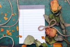 Roses oranges sèches et carnet vide sur le fond en bois, Image stock