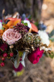 Roses and other flowers inside marsala wedding bouquet Stock Image