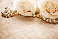Roses and pearls. On an antique book Stock Images