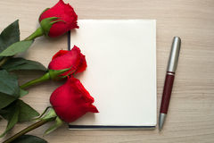 Roses, a pen and a blank piece of paper on the table Stock Photos