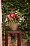 Roses and peons in vase on table close-up. Roses and peons in vase on table, brick floral wall Stock Photo