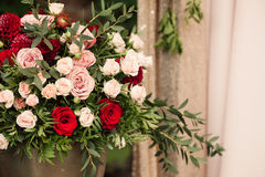 Roses and peons in vase on table close-up. Roses and peons in vase on table, brick floral wall Stock Photos