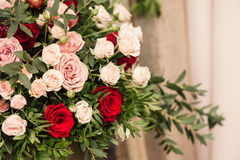 Roses and peons in vase on table close-up. Roses and peons in vase on table, brick floral wall Royalty Free Stock Images