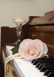 Roses on a piano. Rose sitting on piano keys with a lce glove and a string of pearls, and a candle in the background Stock Photo