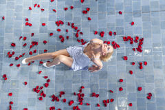 Roses raining on a woman in the  pool Stock Photo