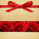 Roses and red bow on carton Royalty Free Stock Photo
