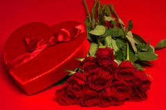 Roses and a red heart box on a red background Royalty Free Stock Photos