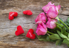 Roses and Red heart pillow on old wooden board, Valentines Day b royalty free stock photography
