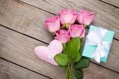 Roses roses au-dessus de table en bois avec le boîte-cadeau et lui de jour de valentines Images stock