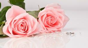 Roses roses avec la bague à diamant sur le fond blanc Photographie stock libre de droits