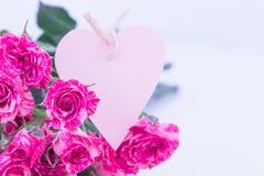 Roses roses avec la carte de coeur Photographie stock libre de droits