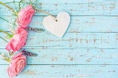 Roses roses avec le coeur sur le bois bleu en pastel Photo stock