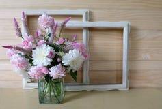 Roses roses, crête, fleur blanche dans un vase et cadre de vintage Photos stock