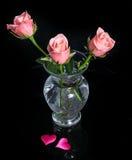 Roses roses dans un vase en verre et deux coeurs sur le noir Photos stock