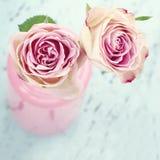 Roses roses dans une bouteille sur le fond en bois Photographie stock libre de droits