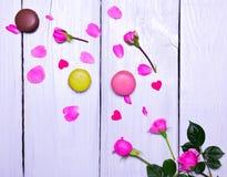 Roses roses de floraison et trois macarons Photographie stock libre de droits
