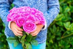 Roses roses lumineuses dans des mains de l'enfant Image libre de droits