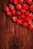 Roses rouges au-dessus de fond brun en bois Photos stock