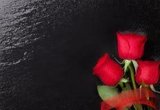 Roses rouges au-dessus de fond en pierre noir Images libres de droits