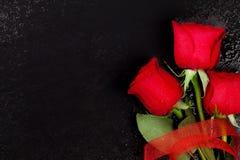 Roses rouges au-dessus de pierre noire Photos libres de droits