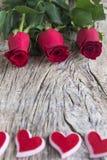 Roses rouges avec des coeurs sur le bois texturisé pour le jour du ` s de valentine Photos stock