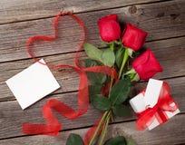 Roses rouges avec la carte de voeux et le cadeau de jour de valentines Photographie stock libre de droits