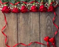 Roses rouges avec le cadre de ruban et deux coeurs Photo stock