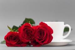 Roses rouges avec une tasse de café de couleur blanche sur un fond gris Photographie stock