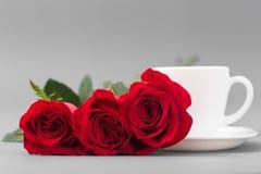Roses rouges avec une tasse de café de couleur blanche sur un fond gris Photographie stock libre de droits