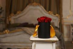Roses rouges dans la boîte noire  Photo stock