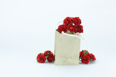 Roses rouges dans le sac de papier sur le fond blanc Photos stock