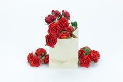 Roses rouges dans le sac de papier sur le fond blanc Photo stock