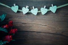 Roses rouges de Valentine avec des coeurs sur le vieux fond en bois Photo stock