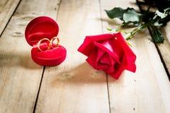 Roses rouges et anneaux de mariage sur en bois Photo libre de droits