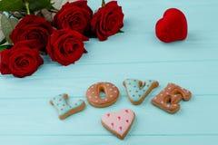 Roses rouges et biscuits de lettre Images stock