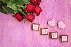 Roses rouges et biscuits roses dans la forme du mot d'AMOUR, sur en bois rose Photo stock