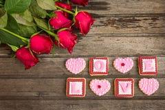 Roses rouges et biscuits roses dans la forme du mot d'AMOUR, sur le dos en bois Photos stock