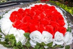 Roses rouges et blanches en forme de coeur épousant le bouquet de fleur devant nouvellement la voiture du ` s de couples d'épouse Photos stock