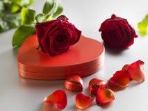 Roses rouges et boîte avec les coeurs rouges sur un fond blanc Photo stock