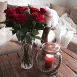 Roses rouges et bouteille en verre avec la lueur d'une bougie photographie stock libre de droits