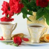 Roses rouges et des cuvettes de thé Photos stock