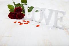 Roses rouges et l'amour de mot Photographie stock