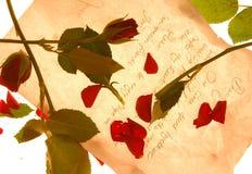 Roses rouges et pétales répandus sur une lettre d'amour Images stock
