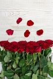 Roses rouges et pétales sur un fond en bois clair, vue supérieure Photo stock