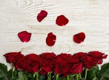 Roses rouges et pétales sur un fond en bois clair, vue supérieure Image stock