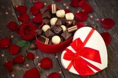 Roses rouges et pralines de chocolat dans le boîte-cadeau en forme de coeur rouge Photo stock