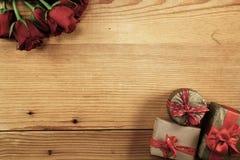 Roses rouges et trois boîte-cadeau sur le bois avec l'espace de copie Photos stock