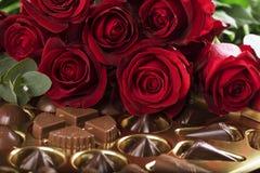 Roses rouges et une boîte de chocolats Photographie stock